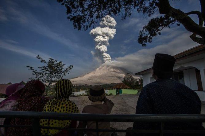 Жители Северной Суматры (Индонезия) наблюдают за извержением вулкана Синабунг